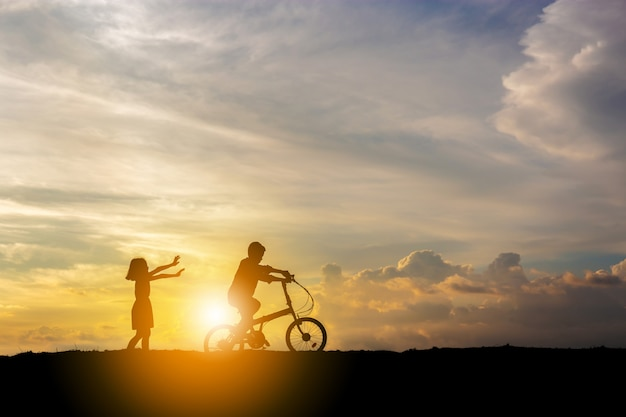 Silhouetten van broer en zus spelen bij zonsondergang avond