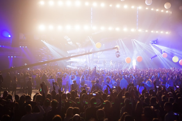 Silhouetten van concertmenigte voor heldere stadiumlichten