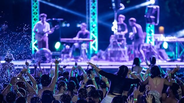 Silhouetten van concertmensen voor heldere podiumverlichting, zwembadfeest