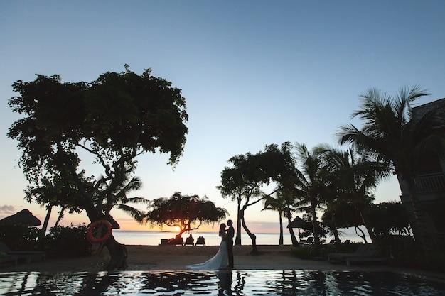 Silhouetten van de bruid en bruidegom bij zonsondergang. de weerspiegeling in het zwembad