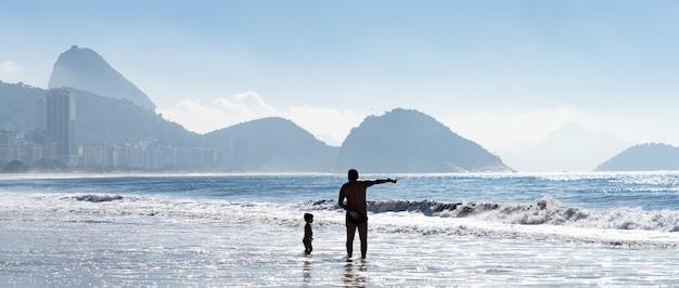 Silhouetten van de vader en het kind spelend aan de kust van de zee in brazilië