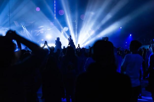 Silhouetten van een concertmenigte en cameraman tegen de achtergrond van heldere, kleurrijke stralen op het podium. camera met de machinist staat op het hoge platform.