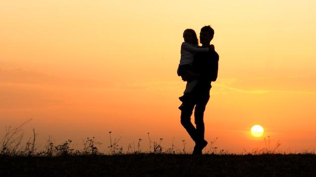 Silhouetten van een gelukkig kind in de armen van de vader