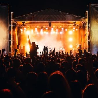 Silhouetten van een hoofd en handen van een menigte van fans op een live concert
