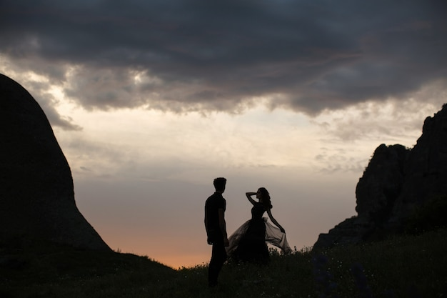 Silhouetten van een jong koppel liefhebbers bij zonsondergang in stralen van de ondergaande zon