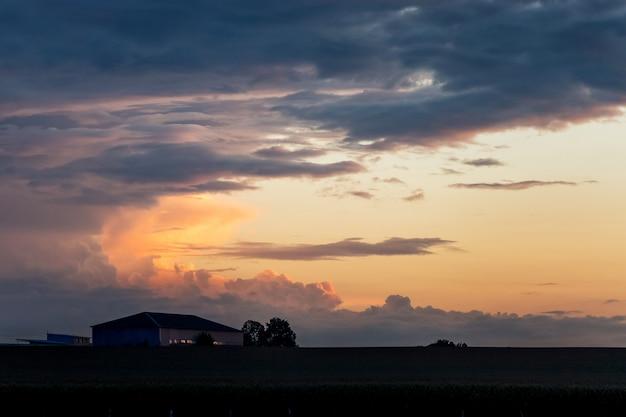 Silhouetten van gebouwen tegen de achtergrond van een dramatische hemel met wolken in de avond