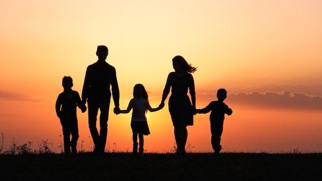 Silhouetten van gelukkige familie die de handen vasthoudt in de weide tijdens zonsondergang