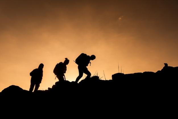 Silhouetten van groep wandelaars gaat naar de top