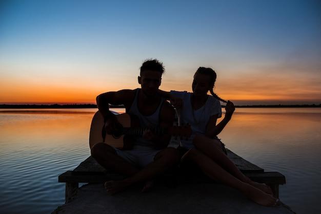 Silhouetten van het jonge mooie paar rusten die zich verheugen bij zonsopgang dichtbij meer
