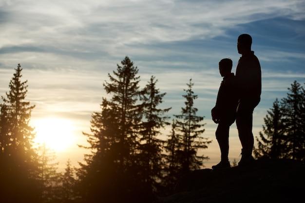 Silhouetten van jonge vader en zoon die 's avonds op de top van de berg staan