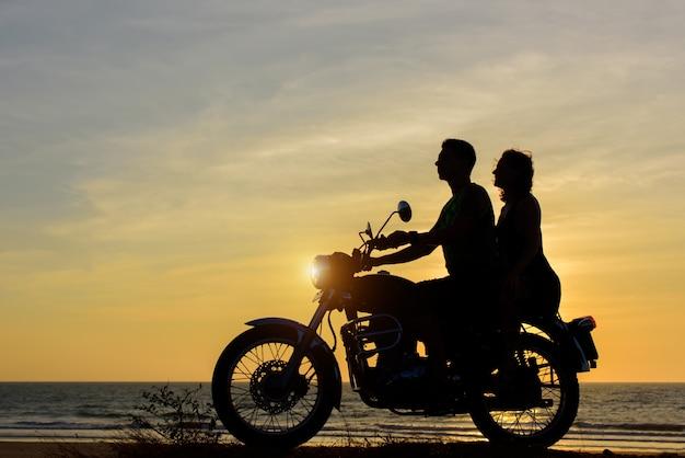 Silhouetten van jongen en meisje op een motorfiets op zonsondergang achtergrond.