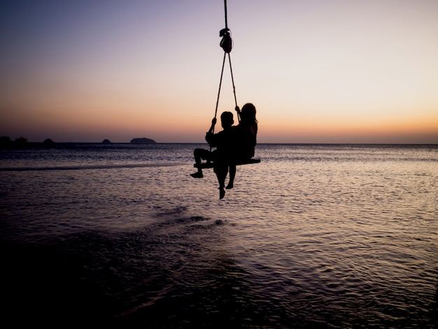 Silhouetten van kinder touw schommels op de gouden uur zonsondergang zee achtergrond.