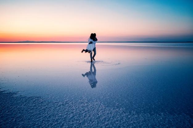 Silhouetten van knuffelen gelukkige geliefden in het midden van ondiep water
