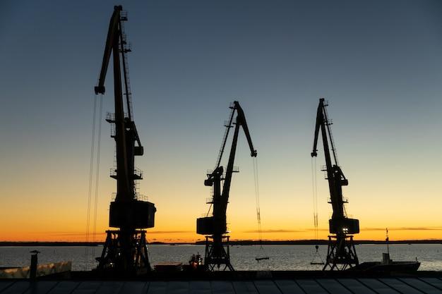 Silhouetten van kranen in de haven in de avond bij zonsondergang