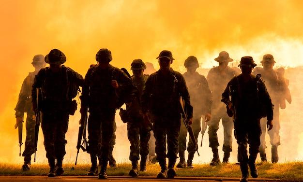 Silhouetten van legersoldaten in de mist tegen een zonsondergang mariniersteam in actie