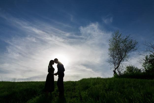 Silhouetten van liefde paren op de natuur in zomeravond. jonge man en vrouw teder omarmen in de zonsondergang