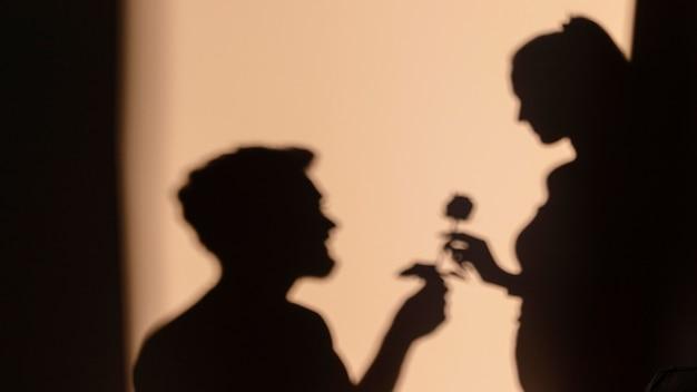 Silhouetten van man en vrouw die thuis een date hebben