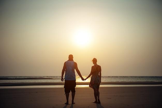 Silhouetten van man en vrouw op het strand. jong koppel in liefde hand in hand bij zonsondergang. concept van liefde, familie, relaties. romantiek, huwelijksreis