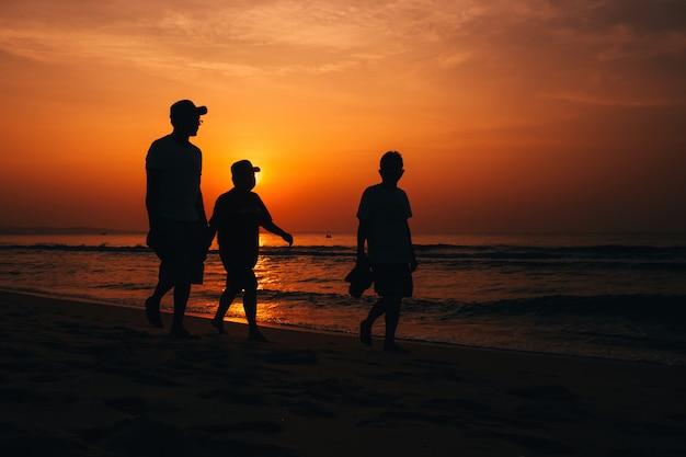 Silhouetten van mannen op het strand aan zee op de achtergrond van de oranje lucht
