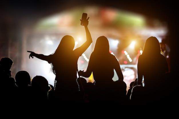 Silhouetten van meisjes bij openluchtmuziekshow.