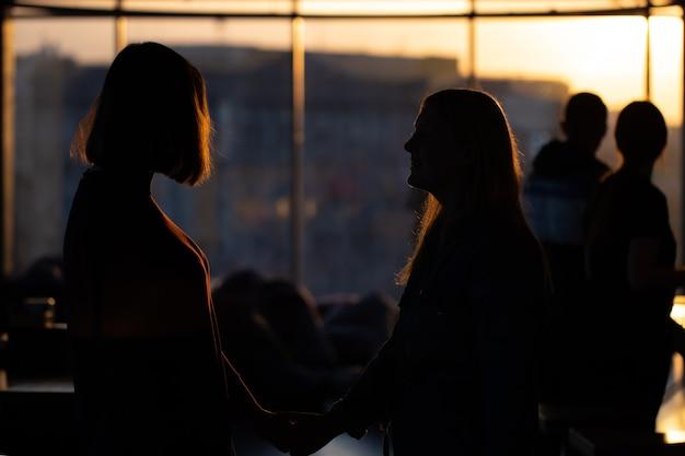 Silhouetten van meisjes die uit het raam kijken naar de zonsondergang
