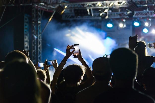 Silhouetten van menigte op concert in de buurt van stadium