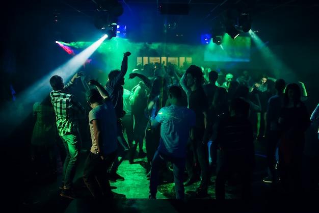 Silhouetten van mensen die in nachtclub op dansvloer bij partij dansen