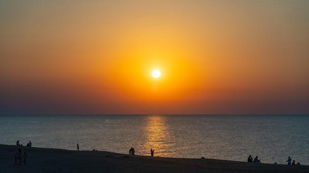 Silhouetten van mensen op het strand bij zonsondergang