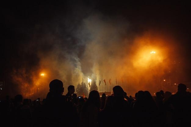 Silhouetten van mensenmassa's die naar het vuurwerk kijken. vier de vakantie op het plein. heel leuk