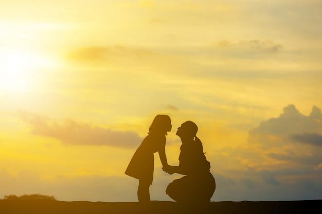 Silhouetten van moeder en dochter spelen bij zonsondergang avond