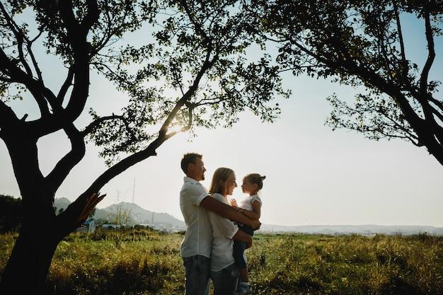 Silhouetten van mooie ouders die met hun dochter onder oude bomen spelen