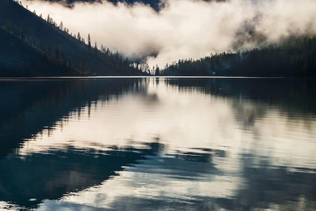 Silhouetten van puntige boomtoppen op heuvel langs bergmeer in dichte mist.