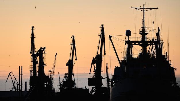 Silhouetten van schepen en containerkranen in zeehaven, avondrood