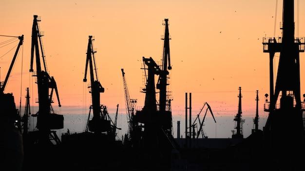 Silhouetten van schepen en containerkranen in zeehaven, zonsondergang