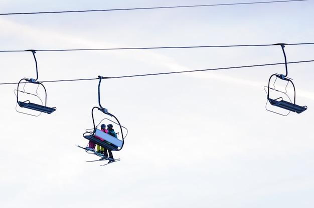 Silhouetten van skiërs op stoeltjesliften in de avond