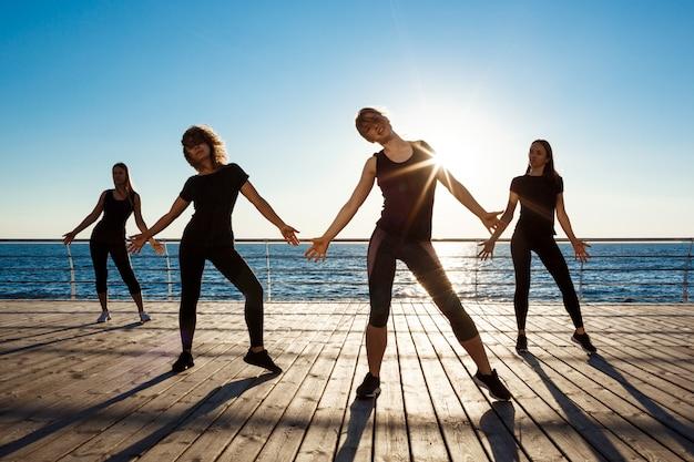 Silhouetten van sportieve vrouwen die dichtbij overzees bij zonsopgang dansen