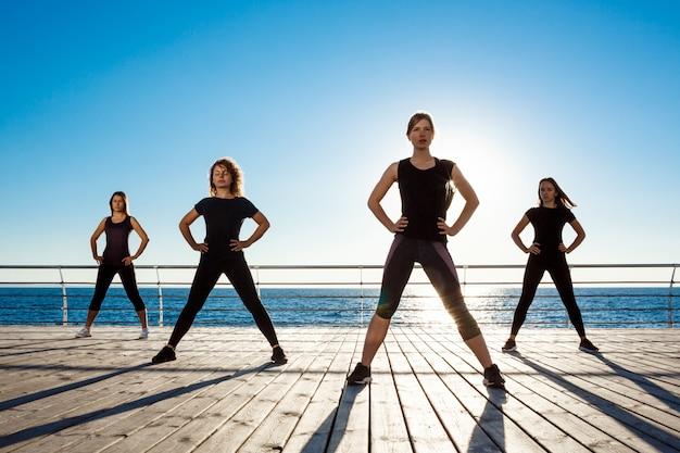 Silhouetten van sportieve vrouwen die zumba dichtbij overzees dansen bij zonsopgang