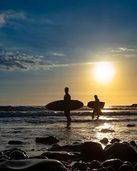 Silhouetten van surfers bij zonsondergang