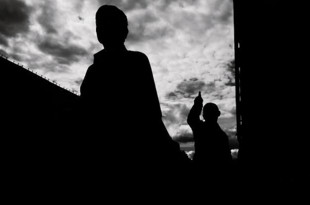 Silhouetten van twee mensen. de een wijst met zijn hand naar de ander.