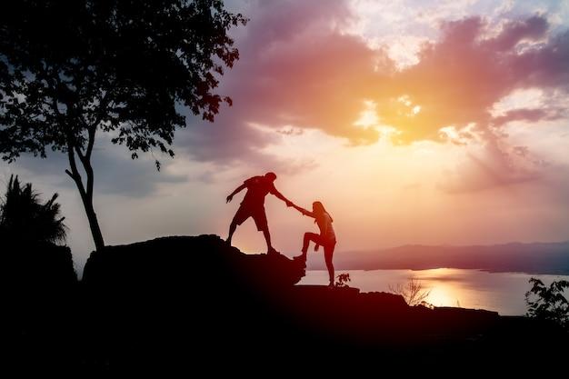 Silhouetten van twee mensen die op berg en het helpen beklimmen.