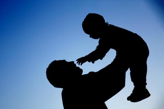 Silhouetten van vader en baby zoon die spelen