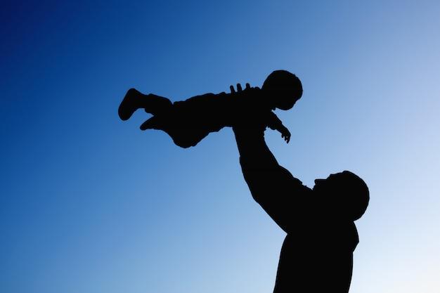 Silhouetten van vader en babyzoon die tegen de blauwe hemelachtergrond spelen. concept van zomervakantie, liefdevolle en vriendelijke familie.
