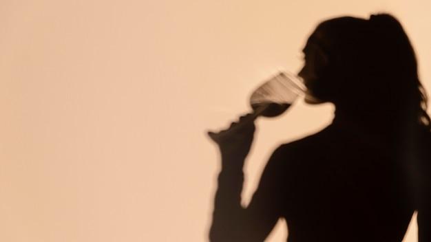 Silhouetten van vrouw die wijn drinkt