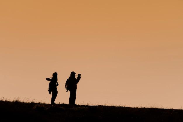 Silhouetten van wandelaars met rugzakken die zonsondergang van mening vanaf bovenkant van een berg genieten