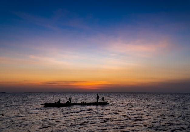 Silhouetvisser op boot op avondrood in de avond