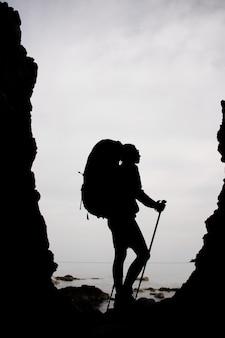 Silhouetvrouw die zich tussen de rotsen op de kustlijn op het overzees met wandelingsrugzak bevinden