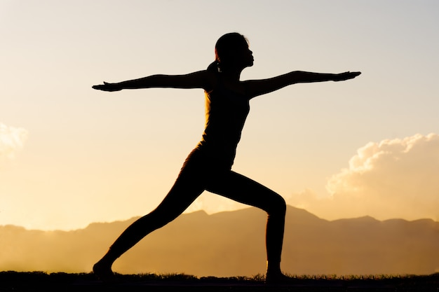 Silhouetvrouw het praktizeren yoga bovenop berg