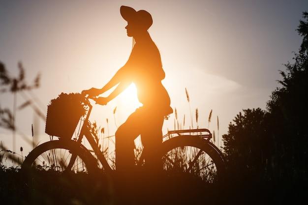 Silhouetvrouw in hoedenzitting op een fiets