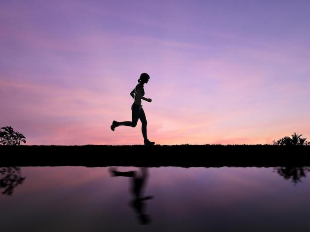 Silhouetvrouw joggen met twilight sky background