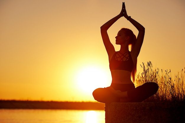 Silhouetvrouw met yogahouding op de strandpijler bij zonsondergang of zonsopgang
